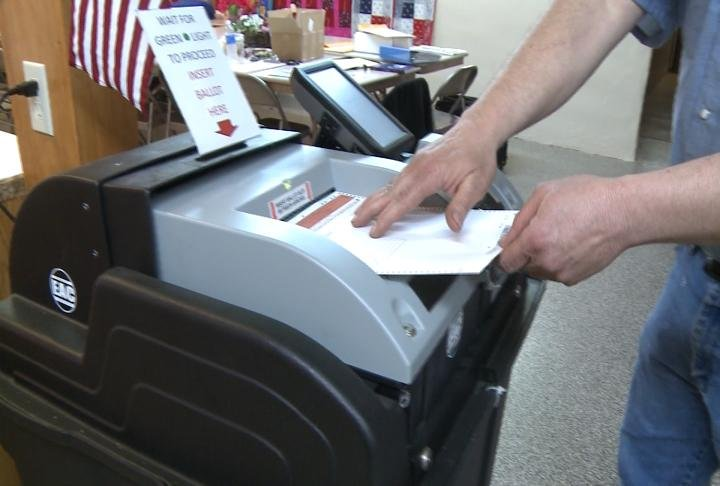Marion County resident adds his ballot to a voting machine.