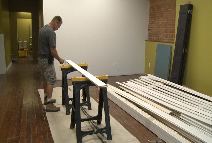 A construction worker paints wood at a new business set to open soon in Mount Sterling.