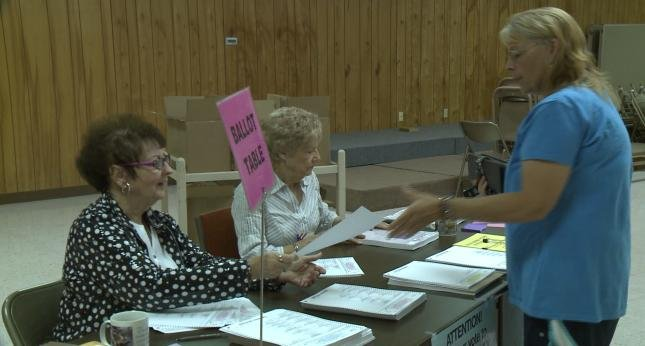 Poll workers sit at a table Tuesday as residents come vote.