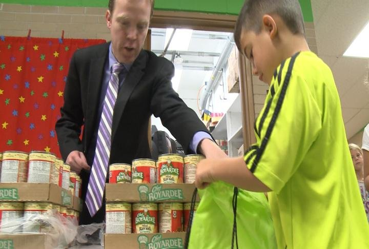 Quincy Mayor Kyle Moore helps pack backpacks with food Thursday morning.