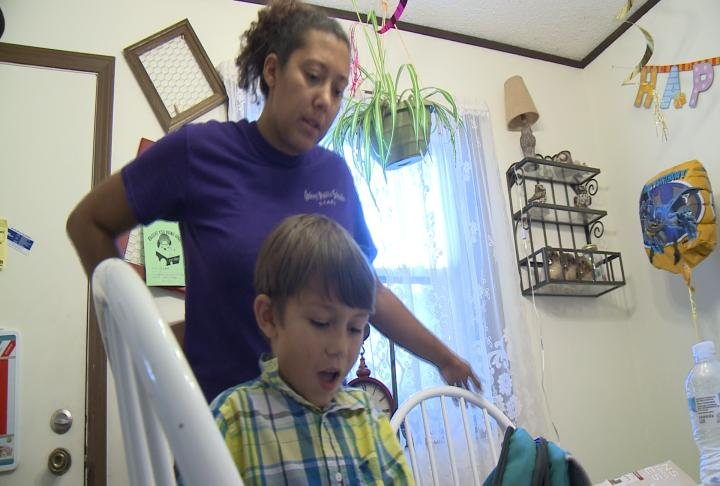 Dickerson helps her son unpack his backpack.