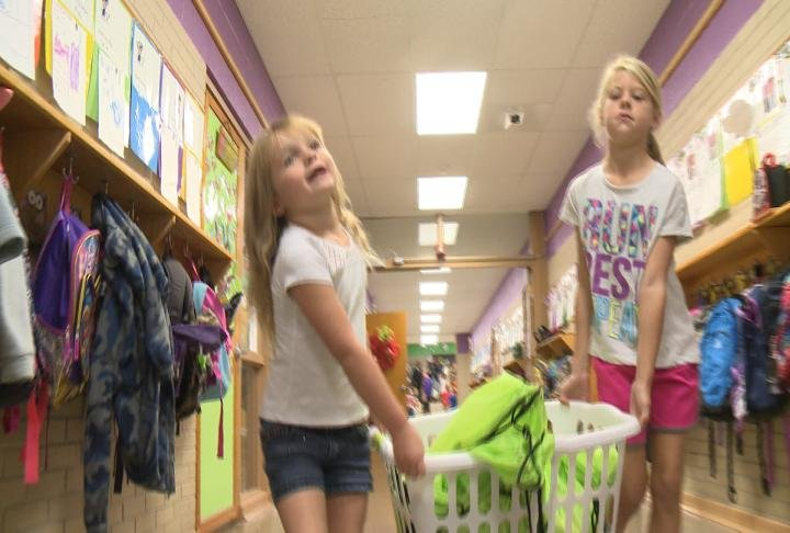 Students help carry backpacks to classrooms at Monroe Elementary School.