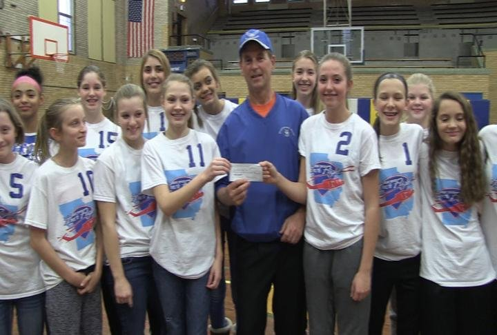 The Lady Blue Devils display a check after raising funds to support the Great River Honor Flight