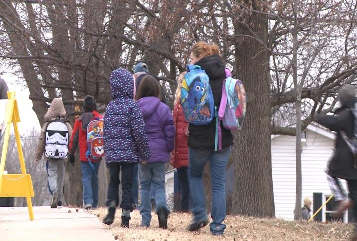 Parents and students walk home from school on Friday.
