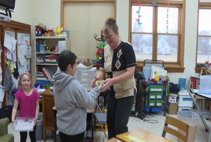 Webster Elementary student CJ Barrientos presented his teacher Shelly Langeland with the WGEM Golden Apple Award.
