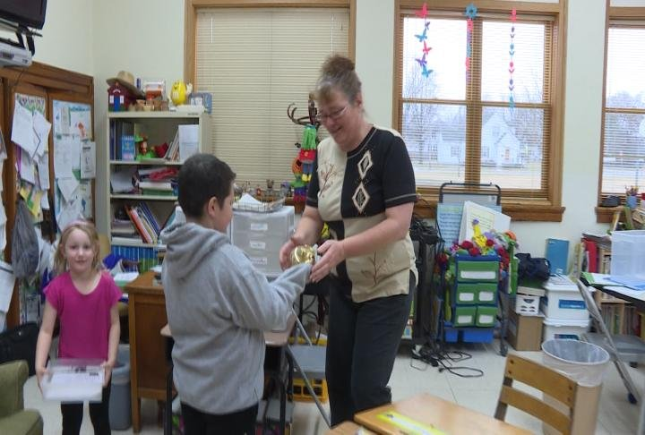 Webster Elementary student CJ Barrientos presented his teacher Shelly Langeland with the WGEM Golden Apple Award.