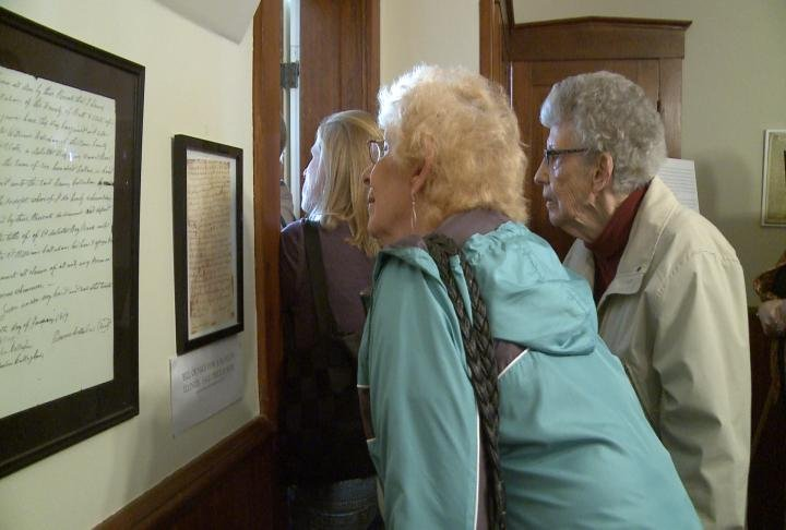 Visitors examine artifacts inside of Dr. Richard Eells' house