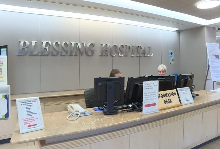 Two workers prepare for questions at Blessing Hospital's information desk.