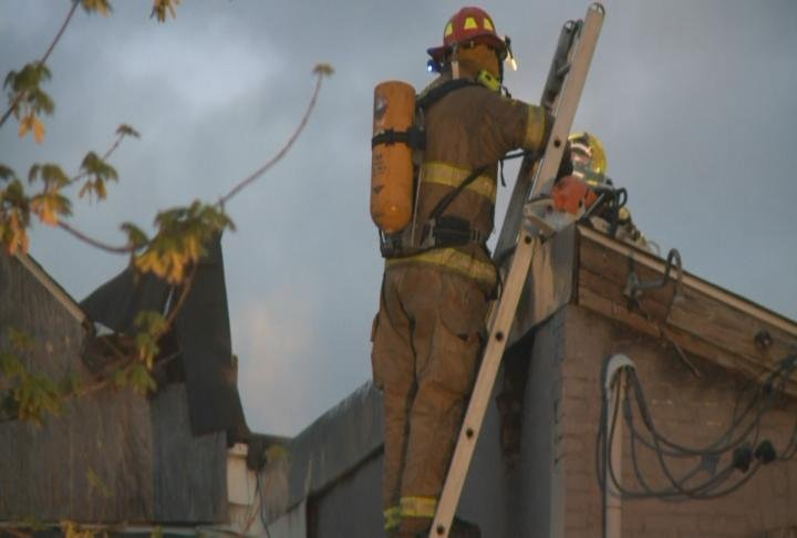 Firefighters work on the roof of the building.
