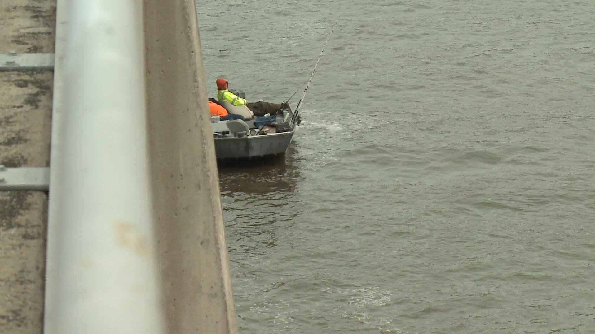 Two boaters fish against one of the gates on the east side of Keokuk's dam, which is illegal.