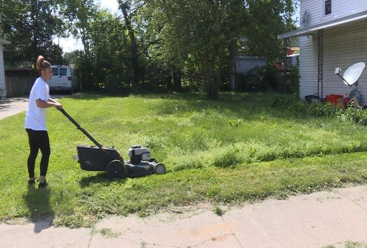 Resident mows her lawn during the day.
