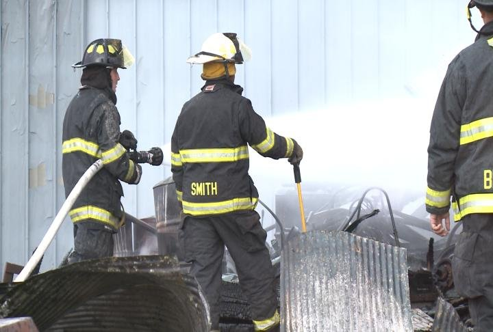 Firefighters put water on the shed to put out remaining flames.