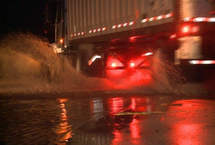 A semi-truck sprays water up driving over a flooded road.