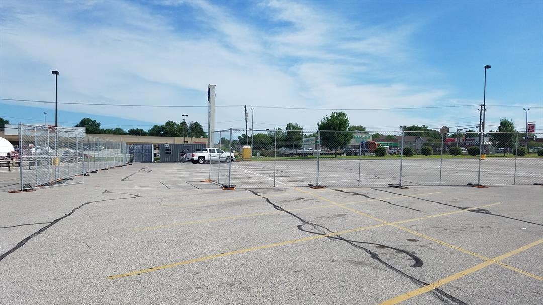 Crews add fencing where construction is about to begin.
