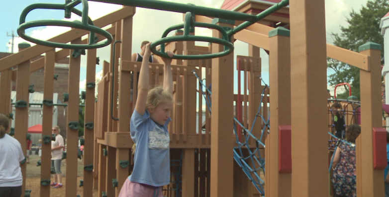 A child swings on one of the park's bars.