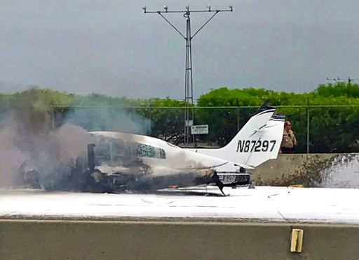 (Wendy Haskell via AP). Flame and smoke erupt from a twin-engine prop jet after it crashed on Interstate 405, just short of the runway at John Wayne Orange County Airport, rear, in Costa Mesa, Calif., Friday, June 30, 2017