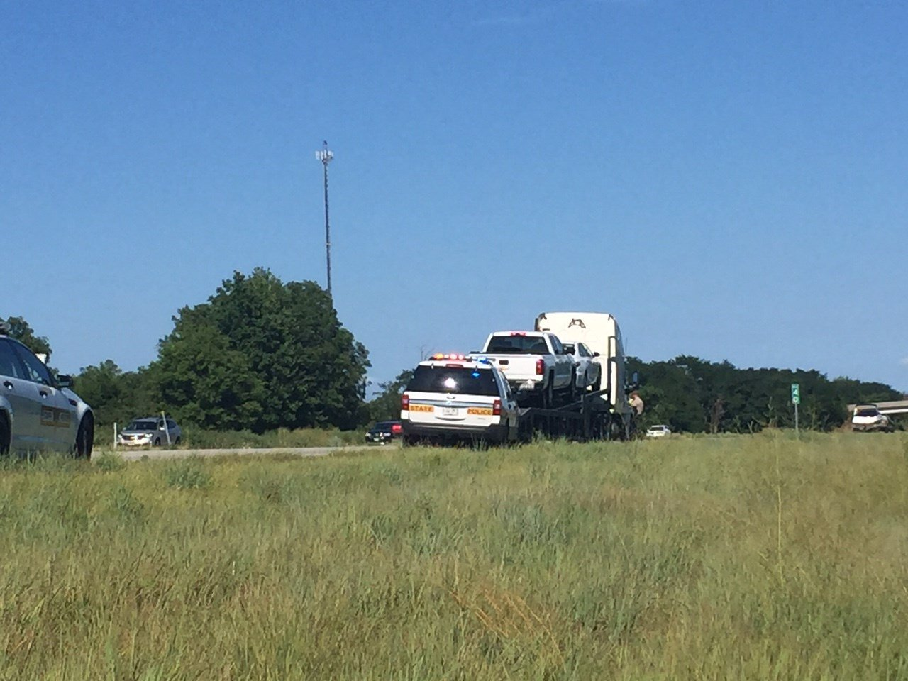 State Police vehicle and truck on the side of the road.