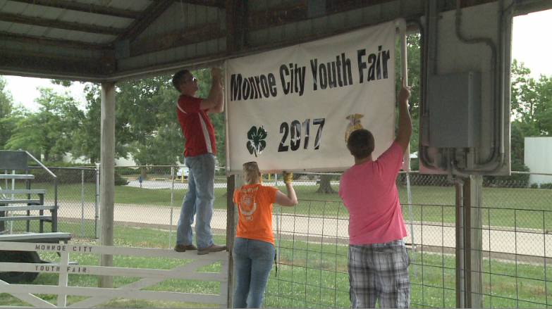 Crews put up the Monroe City Youth Fair sign.