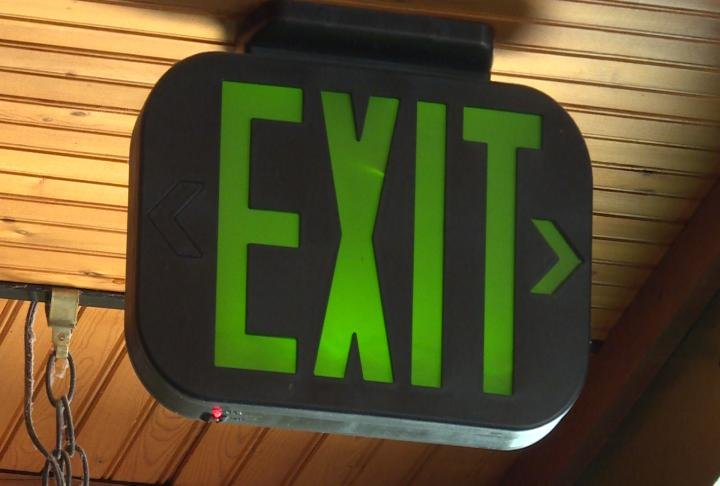 Exit signs hangs near door.