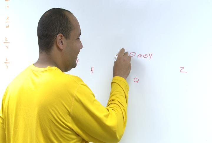 Quincy assistant coach Ben Clark draws up a play in one of the program's new meeting rooms.