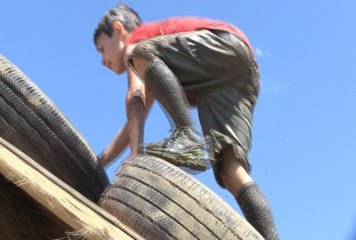 Kids running up the tires in the obstacle course.