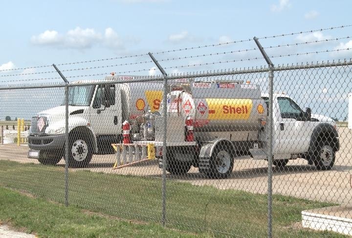 Trucks with tankers parked near Quincy airport runway.