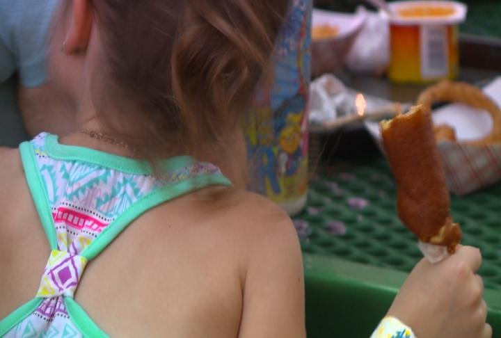 Little girl eats corn dog at Knight of Columbus BBQ.