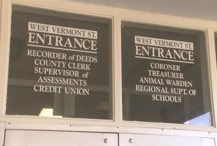 Window decals show list of county offices inside building.