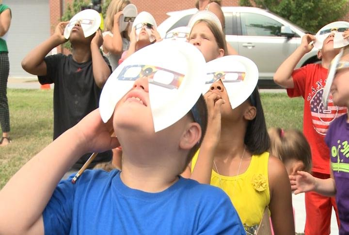 Kids looking up in the sky with their protective glasses.