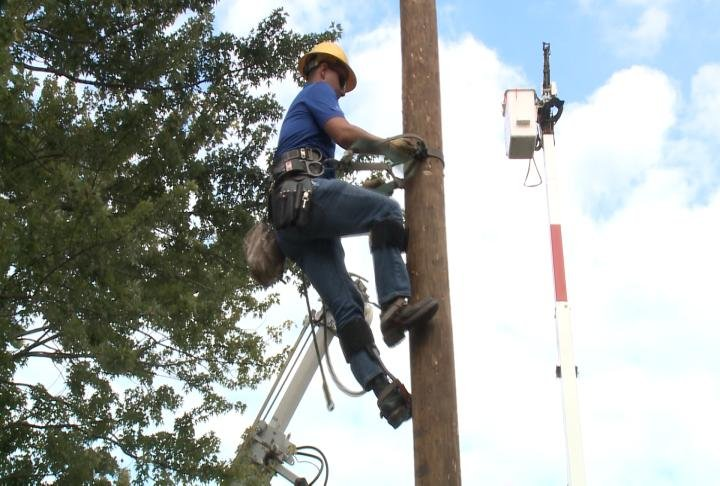 An Adams Electric Coop employee demonstrates how crews work at the company's annual business meeting.