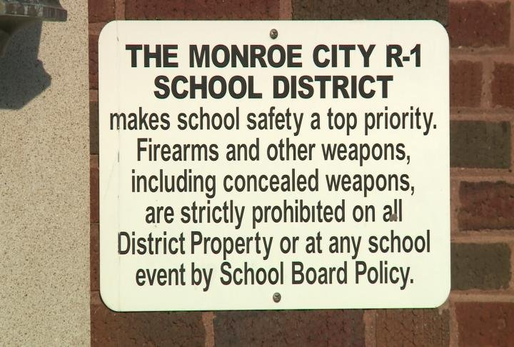 Sign positioned outside a Monroe City School entrance.