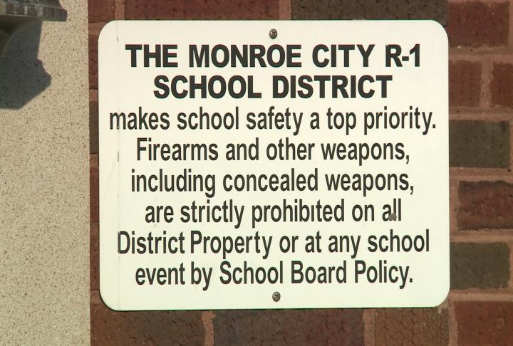 Sign positioned outside a Monroe City School entrance.