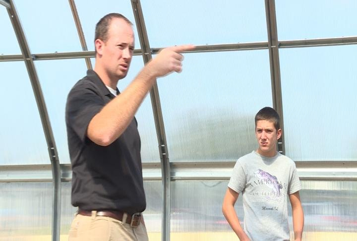 Mr. McGrew teaching students in the greenhouse