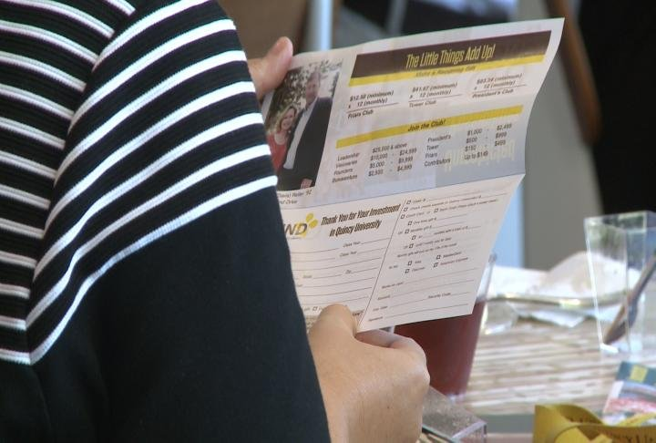 People reading donation pamphlet.