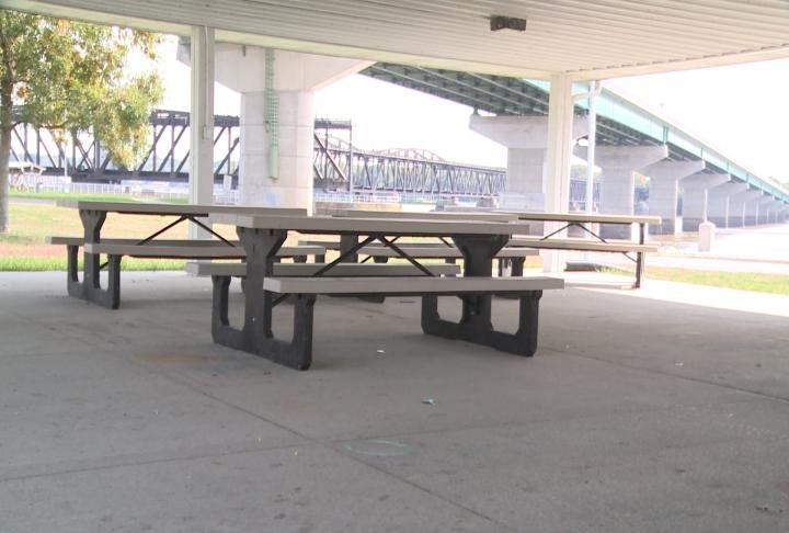 Picnic tables next to the riverfront under the shelter.