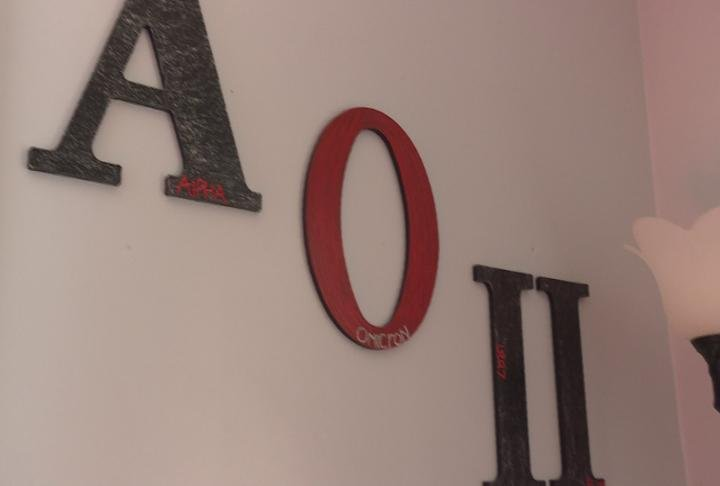 Alpha Omicron Pi sign hangs on the wall.