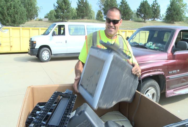 City crews putting TVs into a box to move.