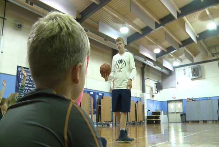 QND senior basketball player Troy Potts talks with Berrian School students at his basketball camp.