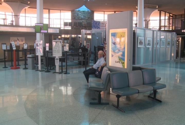 Man sits at Quincy Regional Airport Terminal waiting for flight.