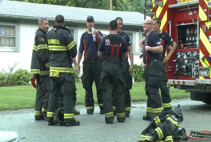 Hannibal Firefighters converse after helping out during an emergency.