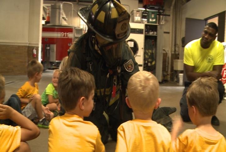 A firefighter crawls around giving high five to students to help get over any fears of the crew.