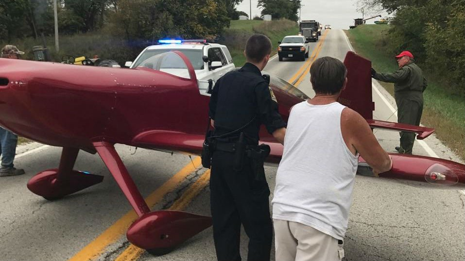 People stand around the plane that made an emergency landing on Illinois 99 Wednesday afternoon