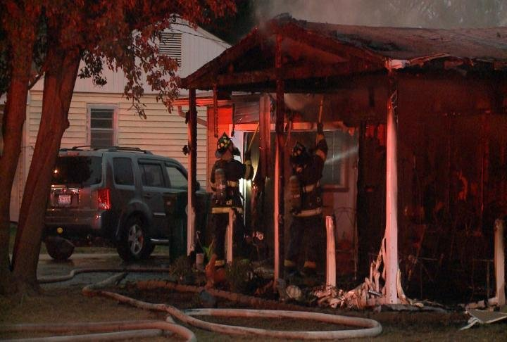 Firefighters tear into the porch to get to a hot spot.