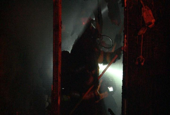 Crews tear through walls while battling fire.