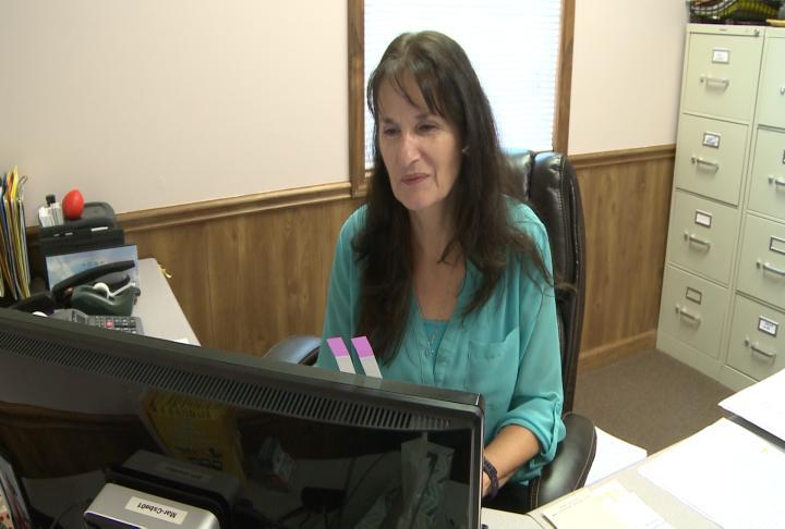 NECAC employee works on computer.
