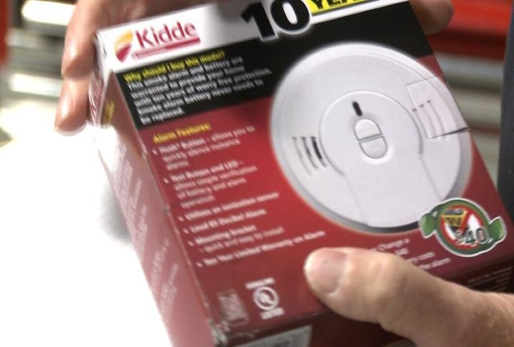 Firefighters shows off smoke detector.