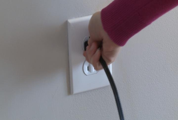 Person plugs cord into wall outlet.