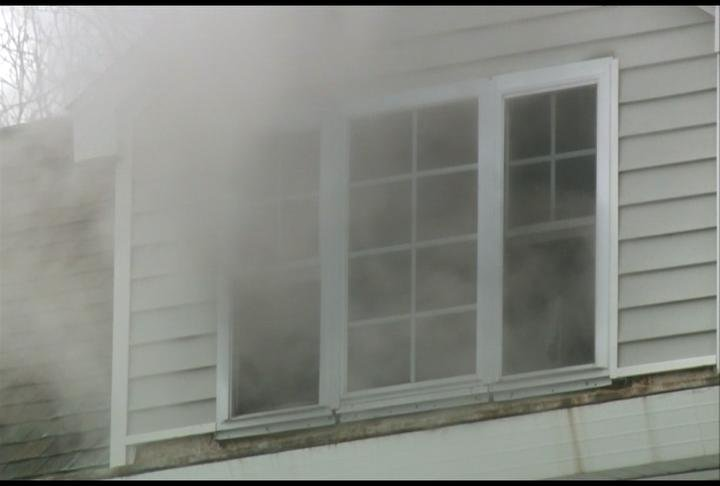 Smoke comes out of a window during a fire.