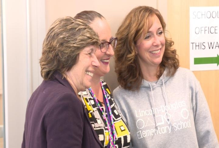 Weingarten posing for a picture with QPS teachers