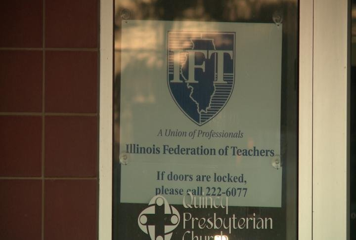 Illinois Federation of Teachers sign hangs in a window.